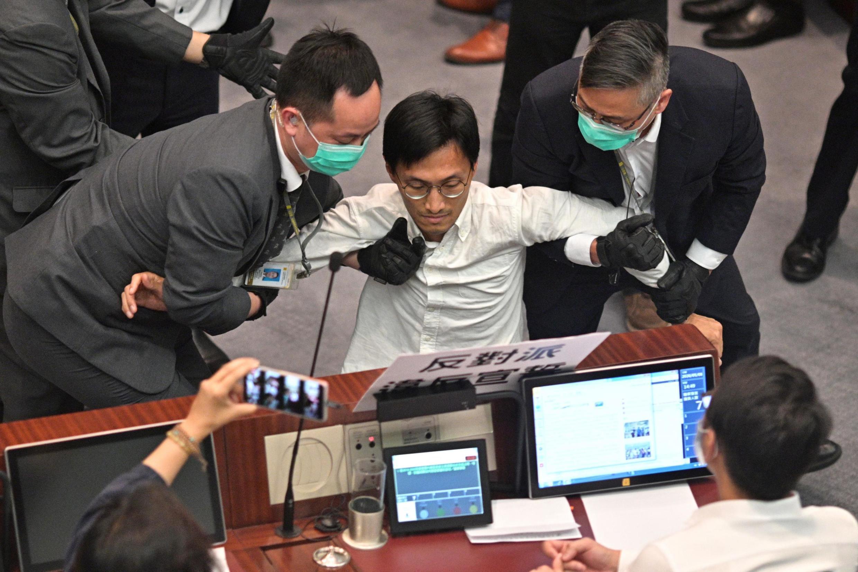 Deputado pró-democracia no parlamento de Hong Kong Eddie Chu Hoi-dick, retido por agentes de segurança, após confrontos na sequência da ocupação da cadeira do diirigente da Comité da Câmra Baixa pela deputada pró-Pequim Starry Lee, sexta-feira 8 de Maio 2020.