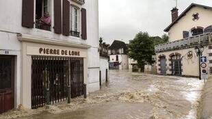 A man looks out of a first floor window watching flood waters sweep through the streets following heavy rains in Salies-de-Bearn, south western France on June 13, 2018.