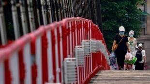 Varias personas con máscaras cruzan el puente colgante de Bitain, en Nueva Taipéi, Taiwán, el 15 de mayo de 2021