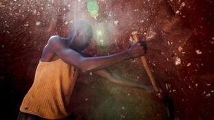 A man digs through some mine waste searching for left over cobalt near Kolwezi