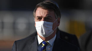 Brazilian President Jair Bolsonaro wears a face mask as he arrives at a flag-raising ceremony at the Alvorada Palace in Brasilia, Brazil, on May 12, 2020