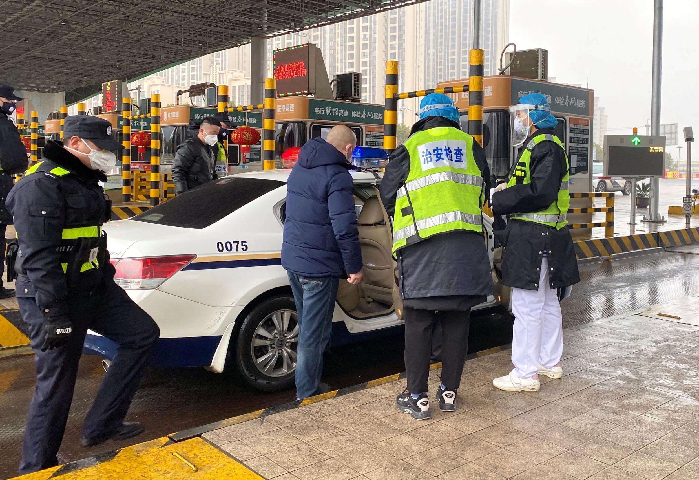 Công an Trung Quốc mang khẩu trang khi kiểm tra xe cộ tại một trạm thu phí để ngăn chận việc buôn lậu động vật hoang dã tại Vũ Hán, ngày 24/01/2020.