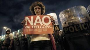 Manifestante posa com cartaz contra a Copa diante da polícia de São Paulo, em 13 de março