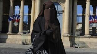 عکس یک زن جوان محجبه با روبند مقابل مجلس ملی فرانسه در سال ۲۰۱۱  میلادی