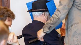 """Bruno Dey, ex-vigia da SS no campo de concentração de Stutthof, esconde o rosto atrás de uma pasta quando chega em uma cadeira de rodas para uma audiência em seu julgamento em 20 de julho de 2020 em Hamburgo, norte da Alemanha. - Os promotores alemães exigiram três anos de prisão para Bruno Dey, um ex-guarda de Stutthof, de 93 anos, que eles disseram ser """"sem dúvida"""" cúmplice no assassinato de mais de 5.000 pessoas."""