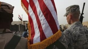 Members of the U.S. military retire its ceremonial flags signifying the end of their presence in Iraq