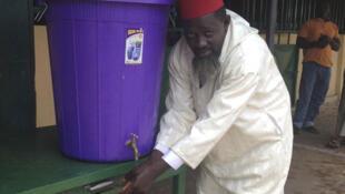 A Conakry, l'imam El Hadj Camara ordonne aux fidèles de se laver les mains avant d'entrer. Ici, il montre l'exemple.
