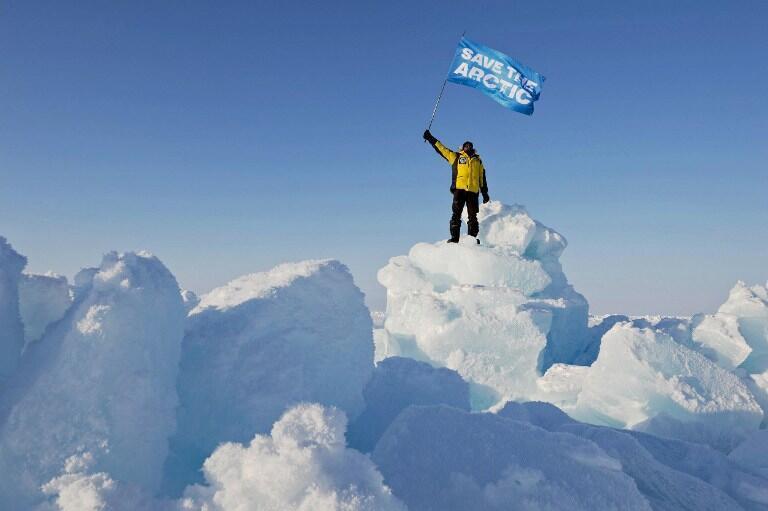 Un militant de Greenpeace brandit un drapeau « Sauvons l'Arctique » au pôle Nord.