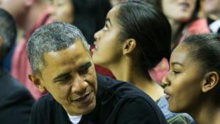 Le président américain avec sa fille Sasha et Michelle Obama lors d'une sortie en famille pour un match de basket le 17 novembre 2013.