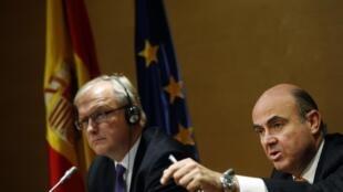 O comissário europeu Olli Rehn (à esquerda) em entrevista coletiva ao lado do ministro da Economia espanhol, Luis de Guindos.