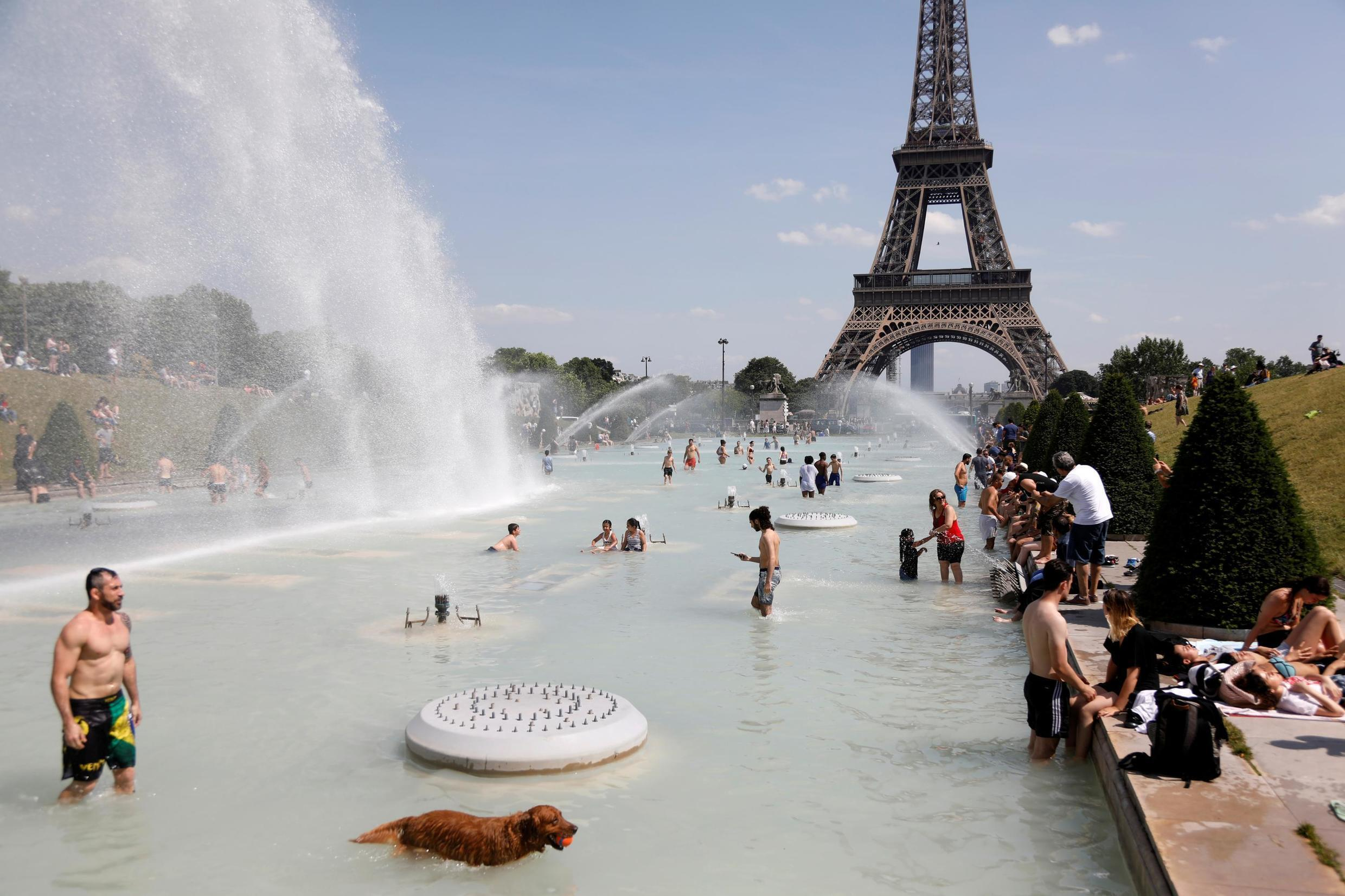 People cool off in the Trocadero fountains across from the Eiffel Tower in Paris as a July heatwave hit much of the country .