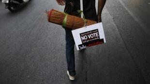 Um manifestante anti-governamental com cartaz pedindo para as pessoas não votarem nas eleições antecipadas.