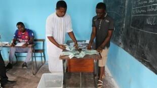 Les responsables électoraux comptent les votes à l'intérieur d'un bureau de vote du quartier Mbouweni à Moroni le 19 janvier 2020.