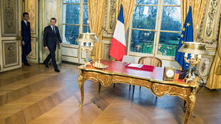 French President Emmanuel Macron and government spokesman Benjamin Griveaux (L) arrive for the signature of three legal texts that will apply in 2018