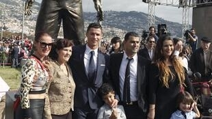 Cristiano Ronaldo e a sua família à frente da estátua.