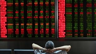 Um investidor olha para as telas que mostram os movimentos do mercado de ações em uma empresa de valores mobiliários em Pequim em 26 de agosto de 2019.