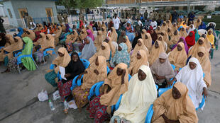 Une partie des lycéennes libérées de Dapchi attendent d'être évacuées par avion à la base aérienne de Maiduguri, au Nigeria, le 21 mars 2018.