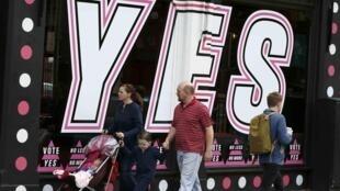 Una familia pasa delante de una tienda decorada en favor del SI en el referendo sobre el matrimonio homosexual.