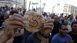Un Palestinien brandit un pain pita «Cher uniquement sur les marchés palestiniens» au cours d'une manifestation à Ramallah en Cisjordanie, le 5 septembre 2012.