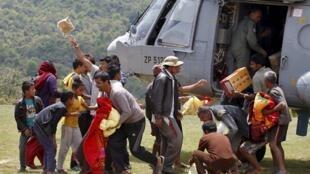 尼泊尔村民从一架印度空军直升机上领取救援物资。2015-05-01