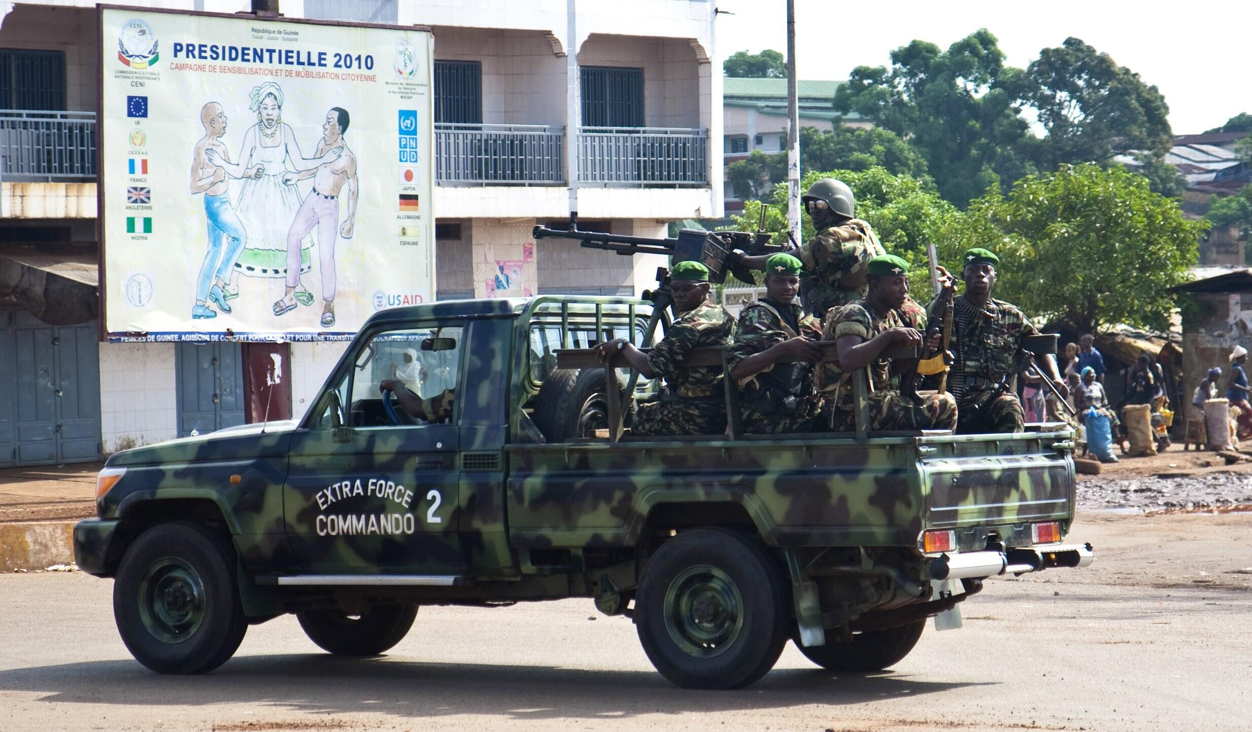 Members of the Guinean military ride on a pick-up truck as they patrol outside Conakry