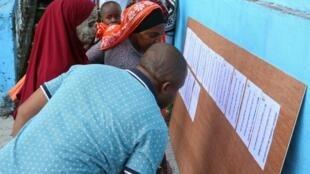 Des électeurs vérifient les listes à l'entrée d'un brueau lors du second tour des législatives, le 236 février 2020.