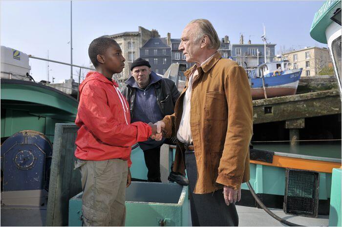 """Cậu bé Idrissa (B.Miguel) và nhà văn Marcel (André Wilms) trong phim """"Le Havre"""" của đạo diễn Aki Kaurismäki (Pyramide Distribution)"""