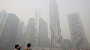 Du khách đi tham quan các cao ốc tại Singapore phải đeo khẩu trang do khói bụi.