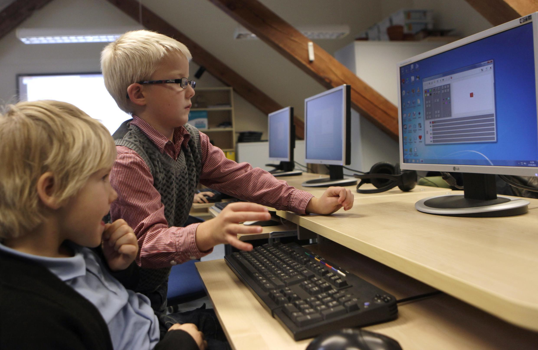 Crianças usando internet para fazer trabalho escolar.