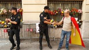 Un partisan de l'unité de l'Espagne serre la main à un policier à Barcelone en marge d'une manifestation anti-indépendance, le 20 octobre 2019.