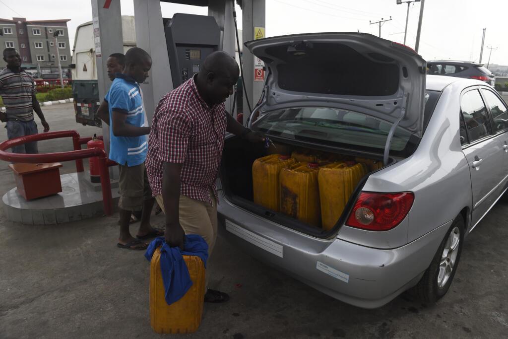 Un homme charge des bidons d'essence dans sa voiture le 21 décembre 2017 à Lagos, au Nigeria, alors que le pays est touché par les pénuries de carburants.