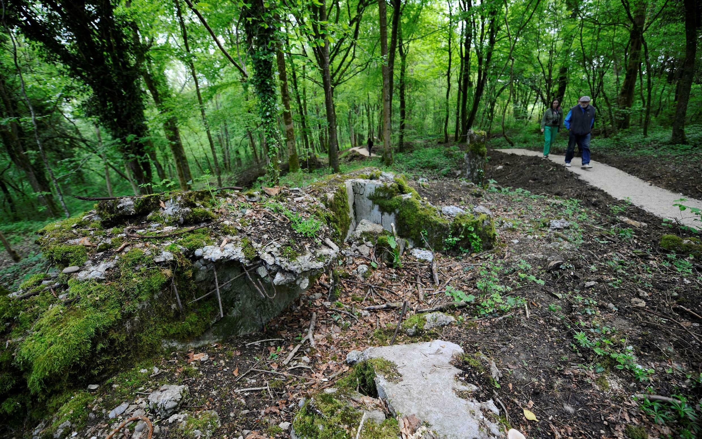 Pessoas caminham na floresta de Verdun para visitar as ruínas da batalha de Verdun.
