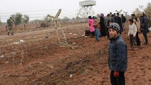 Syrian refugees wait to enter Turkey after fleeing violence in Syria.