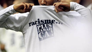 """O jogador Serge Gakpe com uma blusa contra o racismo. """"Racismo nunca mais""""."""