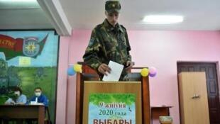 Un soldat biélorusse dépose son bulletin de vote dans l'urne lors de l'élection présidentielle, le 9 août 2020 à Minsk.