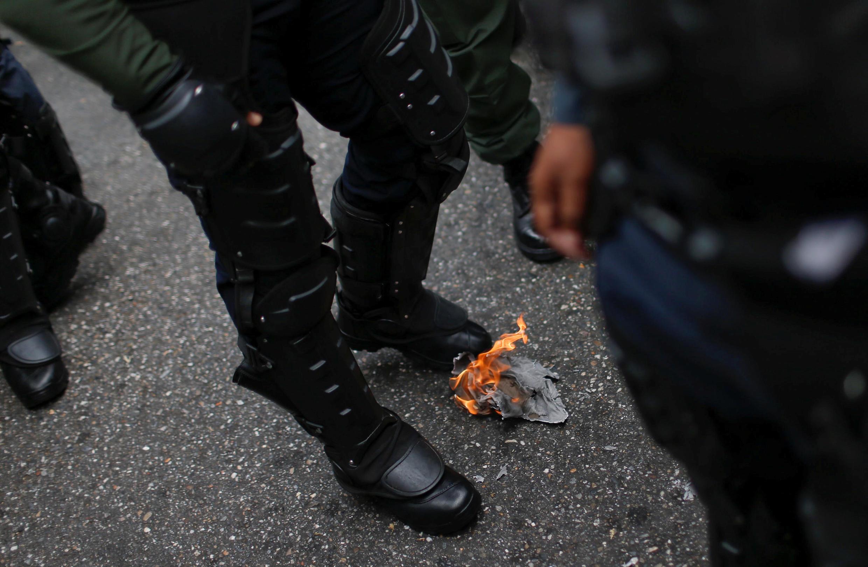 Un membre de la garde nationale brûle un message remis par un opposant à Nicolas Maduro, samedi 4 mai.