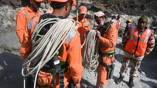 Rescuers prepare for an operation near a tunnel blocked with mud and debris