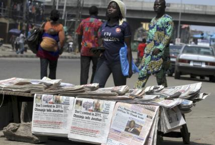 People walk past a newspaper stand in Ikeja district in Nigeria's commercial capital Lagos