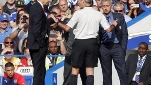 Mai horar da Chelsea Jose Mourinho (dama) da takwaransa na Arsenal Arsene Wenger (hagu) yayinda da alkalin wasa Martin Atkinson ya shiga tsakaninsu yayin wasa tsakanin Arsenal da Chelsea a filin Stamford Bridge. Oktoba 5, 2014.