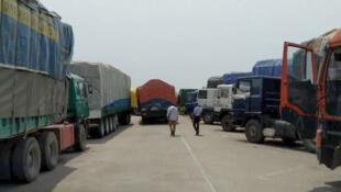 Au poste-frontière de Kraké, le parc réservé aux camions est plein, occupé par d'autres poids lourds et leurs marchandises.