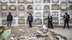 Familiares de un fallecido de covid-19 mantienen distancia en el cementerio de El Angel, en Lima, mientras aguardan el entierro