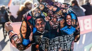 Un manifestante muestra su chaqueta con las caras de afroestadounidenses muertos  o heridos por la policía, durante una concentración en Minneapolis, el 8 de marzo de 2021