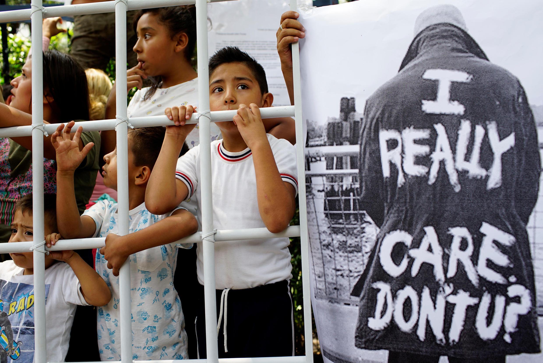Des enfants à l'intérieur d'une fausse cage à côté d'une pancarte en référence à Melania Trump, lors d'une manifestation contre les politiques américaines d'immigration à l'extérieur de l'ambassade américaine à Mexico, le 26 juin 2018.