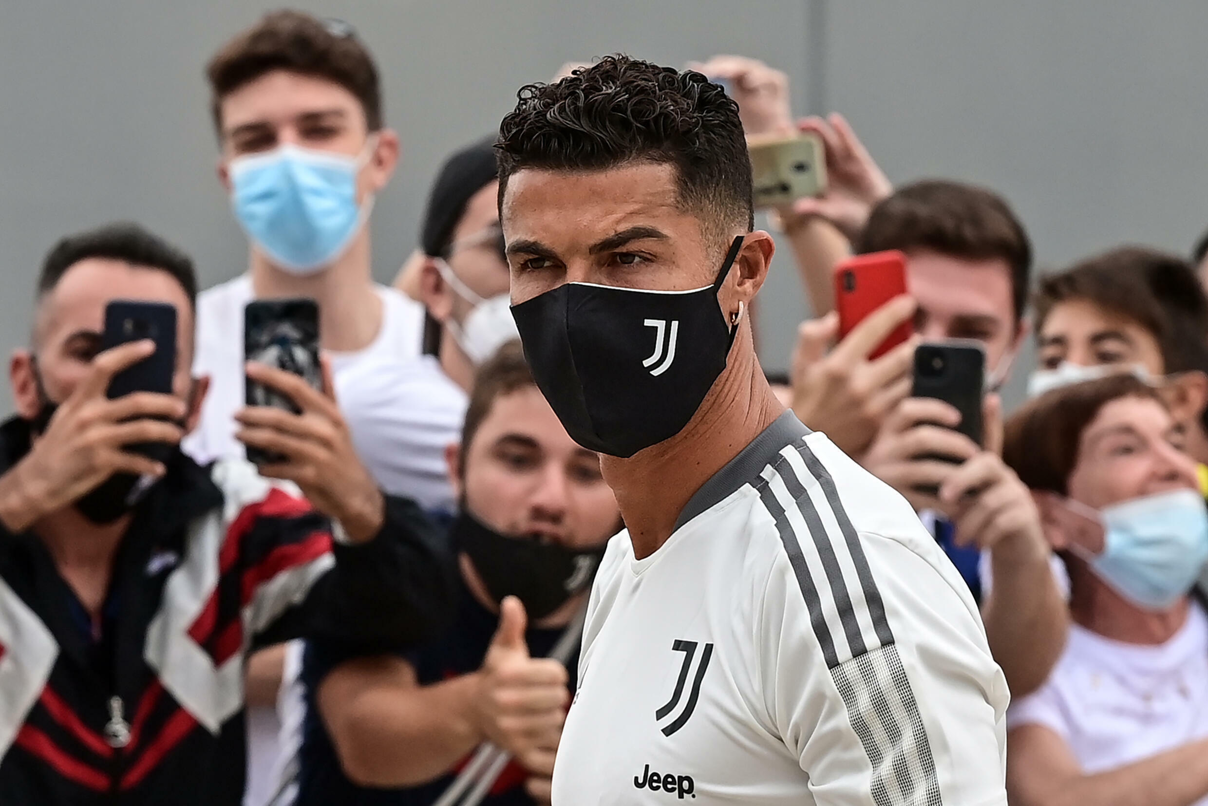 Juventus forward Cristiano Ronaldo is greeted by fans as he arrives for his medical examination at the Juventus medical center in Turin.