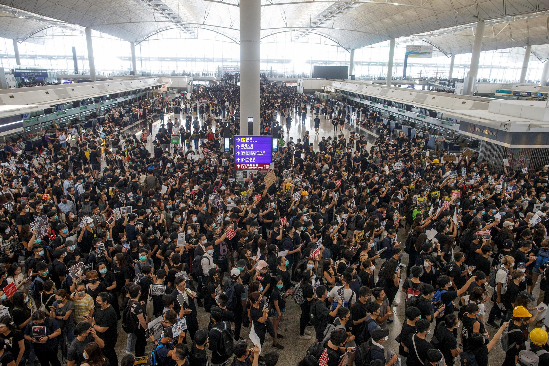 Os manifestantes pró-democracia ocupam o terminal de embarque do aeroporto de Hong Kong, nesta segunda-feira 12 de agosto de 2019.