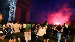 Torcedores argelinos comemoram perto do Arco do Triunfo em Paris a vitória da sua equipe sobre a Costa do Marfim nas quartas de final da Copa Africana de Nações (CAN) de 2019, em 11 de julho de 2019.