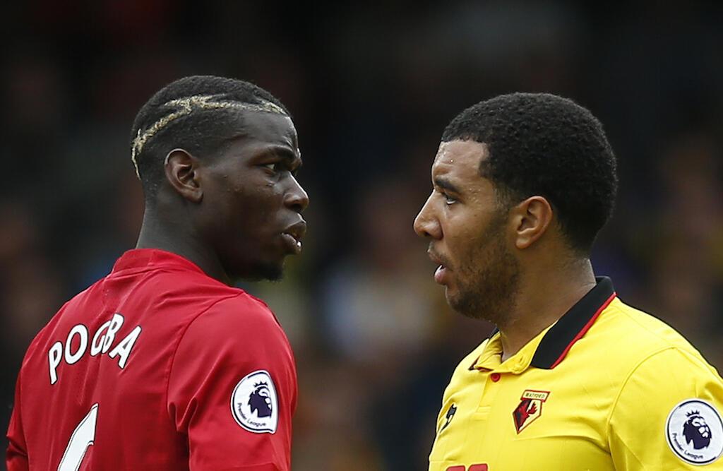 Mchezaji wa Manchester United, Paul Pogba akitunishiana misuli na mchezaji wa Watford, Troy Deeney