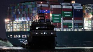 El gigantesco barco carguero Ever Given, encallado en el Canal de Suez, la noche del 27 de marzo de 2021 en Suez (Egipto)