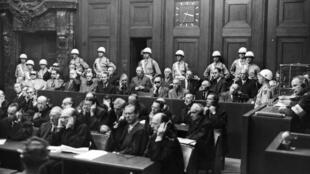 Les principaux accusés dans le «Procès de Nuremberg des grands criminels de guerre». En arrière-plan, la porte de l'ascenseur par laquelle les accusés sont entrés dans la salle. 1945/1946.