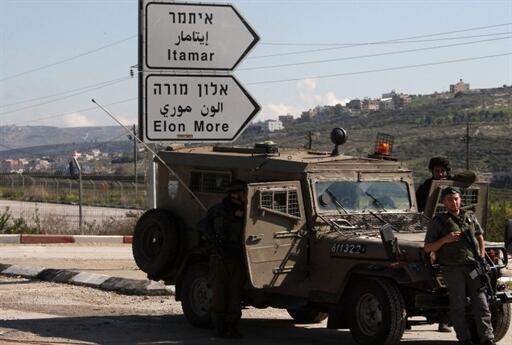 Des soldats israéliens montent la garde à un croisement menant à la colonie de peuplement d'Itamar, dans le nord de la Cisjordanie.
